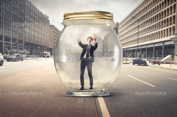 Young man trapped in a glass jar on a city street